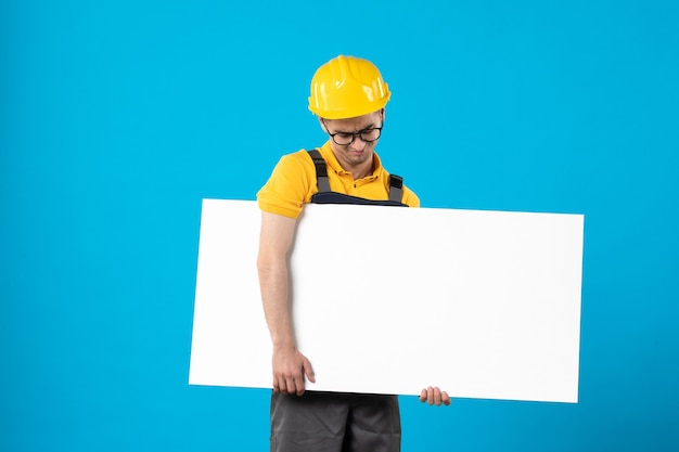 Front view male builder in yellow uniform with plan on blue