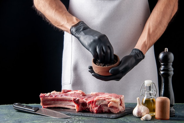 暗い表面の肉スライスにコショウを注ぐ正面図男性肉屋