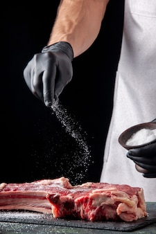 Front view male butcher salting meat on black surface