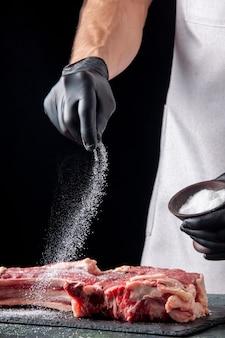 Мужской мясник, соление мяса на темной поверхности, вид спереди