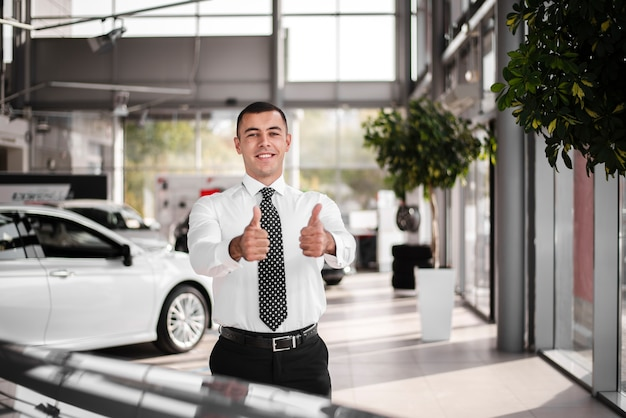 Front view male car dealer showing ok sign