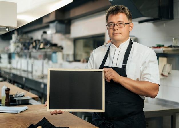 Vista frontale del cuoco unico maschio che tiene lavagna