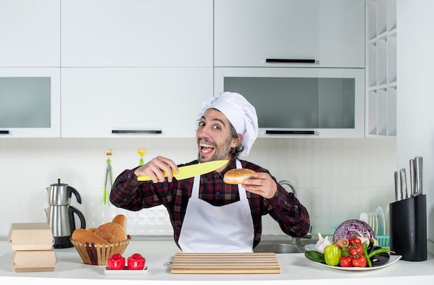Front view of male chef holding bread and yellow knife in the kitchen