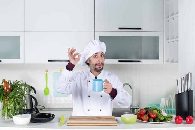부엌 테이블 뒤에 서 있는 요리사 모자를 들고 전면 보기 남성 요리사