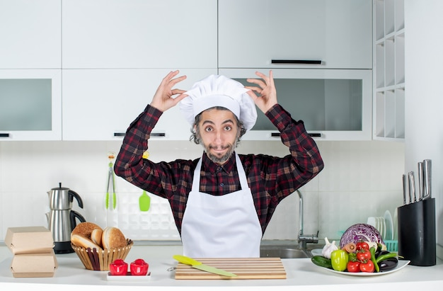 Front view male chef holding his cook hat in the kitchen