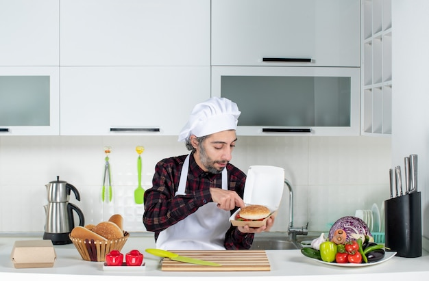 Front view male chef holding up burger in the kitchen