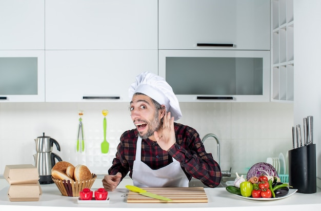 Front view of male chef listening to something standing behind kitchen table in the kitchen