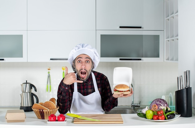 Front view of male chef making call me sign holding up burger in the kitchen