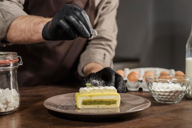 Вид спереди мужской шеф-повар, покрывающий десерт