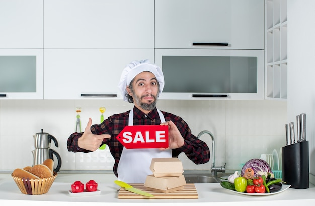 Front view of male chef pointing finger himself holding up sale sign in the kitchen