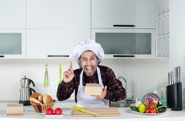 Front view of male chef pointing finger up holding box in the kitchen