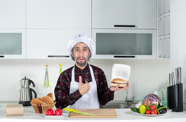 Vista frontale dello chef maschio che indica se stesso tenendo in mano il cartello di vendita e hamburger in cucina