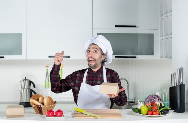 Front view of male chef pointing at behind standing behind kitchen table in the kitchen