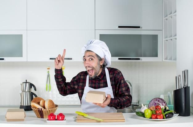 Vista frontale dello chef maschio che sorprende con un'idea che tiene in mano una scatola in cucina