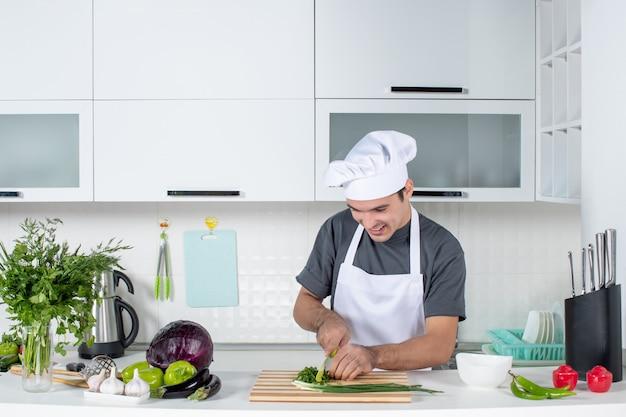 Cuoco unico maschio di vista frontale in uniforme che taglia i verdi dietro il tavolo della cucina