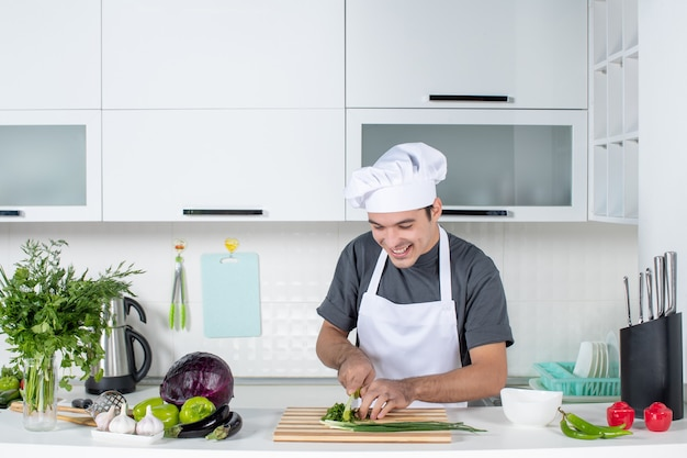 Front view male chef in uniform cutting greens on wood board