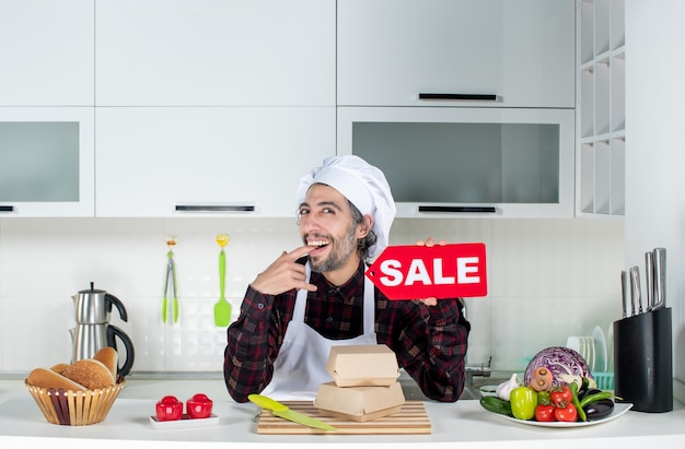 Front view of male chef in uniform holding up red sale sign biting his finger in modern kitchen