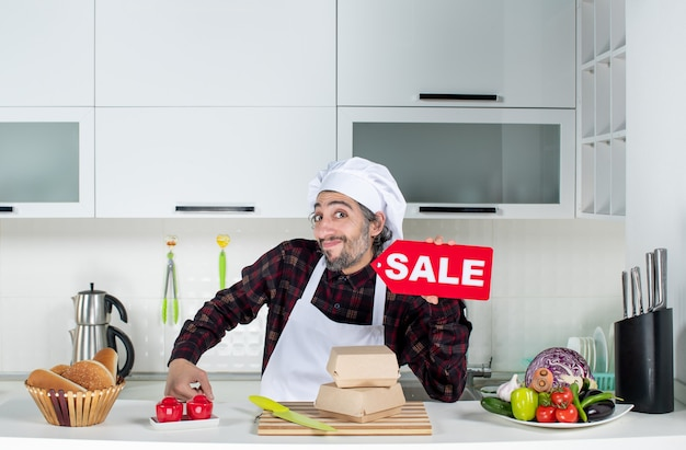 Front view of male chef in uniform holding up red sale sign in the kitchen
