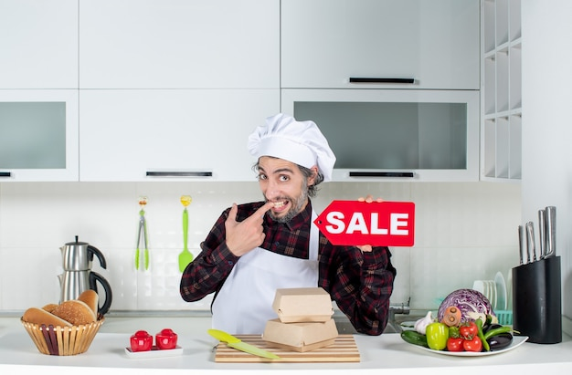 Front view of male chef in uniform holding up red sale sign in modern kitchen