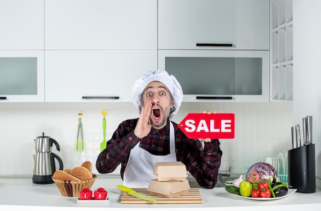 Front view of male chef in uniform holding up red sale sign saying something in modern kitchen
