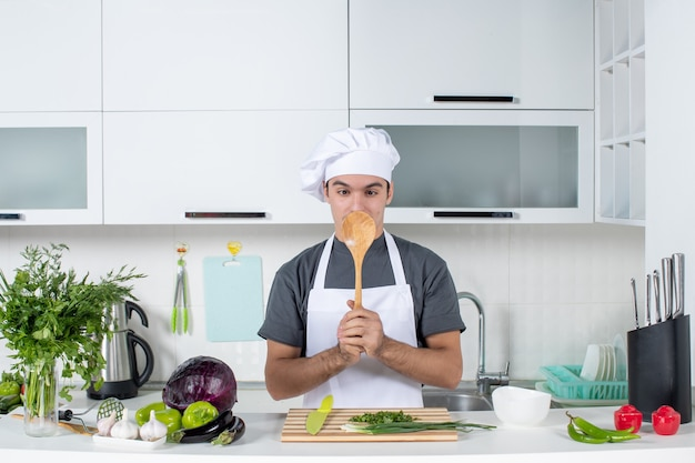 Front view male chef in uniform holding up wooden spoon