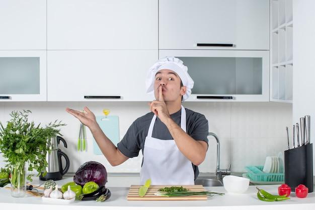 Chef maschio vista frontale in uniforme che fa segno di silenzio dietro il tavolo della cucina
