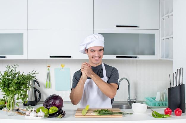 Chef maschio vista frontale in uniforme con le mani giunte dietro il tavolo della cucina