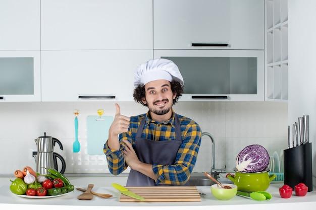 Vista frontale dello chef maschio con verdure fresche e cucinare con utensili da cucina e fare un gesto ok nella cucina bianca