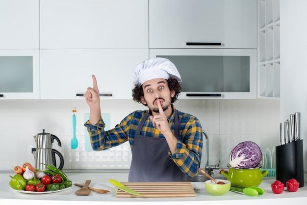 Vista frontale dello chef maschio con verdure fresche e cucina con utensili da cucina e gesto di silenzio rivolto verso l'alto nella cucina bianca