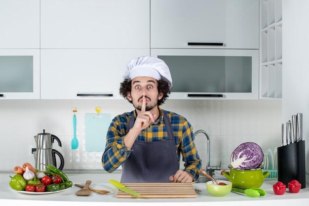 Vista frontale dello chef maschio con verdure fresche e cucina con utensili da cucina e gesto di silenzio nella cucina bianca