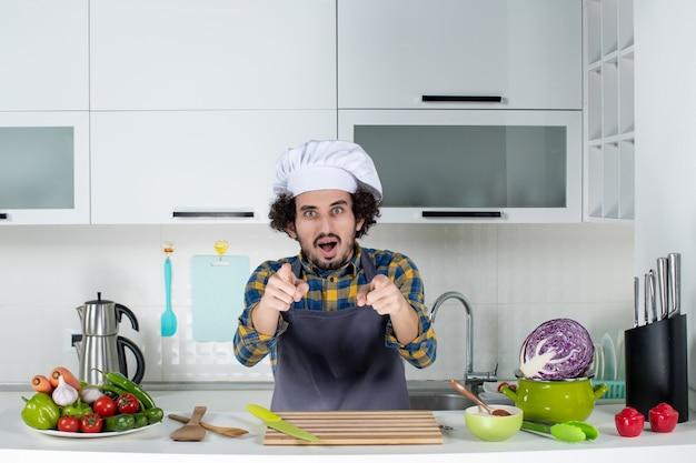 Vista frontale dello chef maschio con verdure fresche e cucina con utensili da cucina e che punta in avanti nella cucina bianca