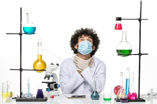 医療スーツを着て、白いスペースに自分自身をむさぼり食うマスクを持った正面図の男性化学者