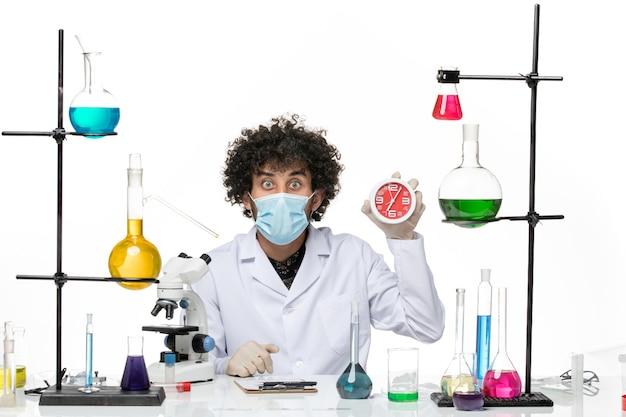 医療スーツと白いスペースに時計を保持しているマスクを持つ男性の化学者の正面図