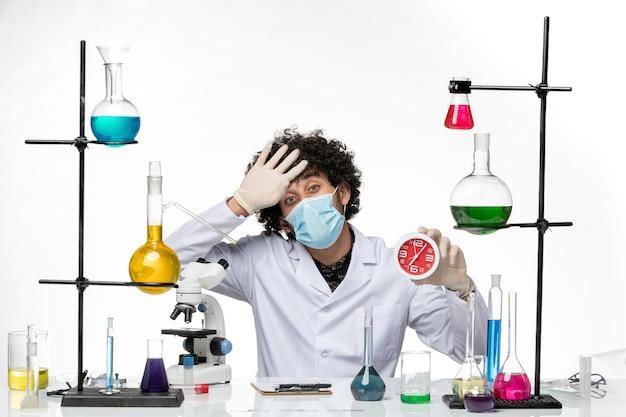 医療スーツと白い机の上に赤い時計を保持しているマスクを持つ男性の化学者の正面図