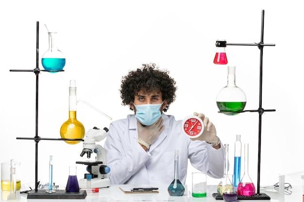 医療スーツと白いスペースに赤い時計を保持しているマスクを持つ男性の化学者の正面図