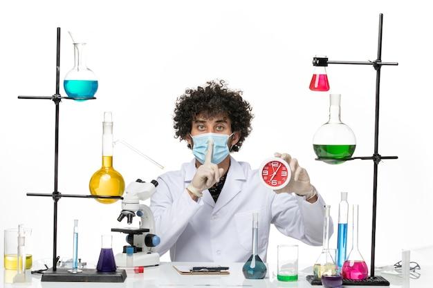 医療スーツを着て、明るい白いスペースに赤い時計を保持しているマスクを持つ男性化学者の正面図