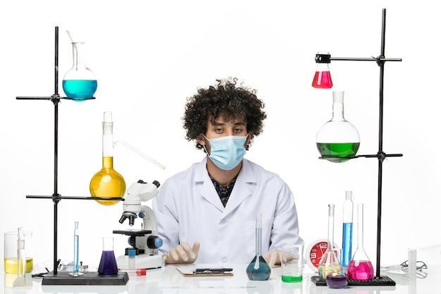 医療スーツを着て、白いスペースにさまざまなソリューションで座っているだけのマスクを持った正面図の男性化学者