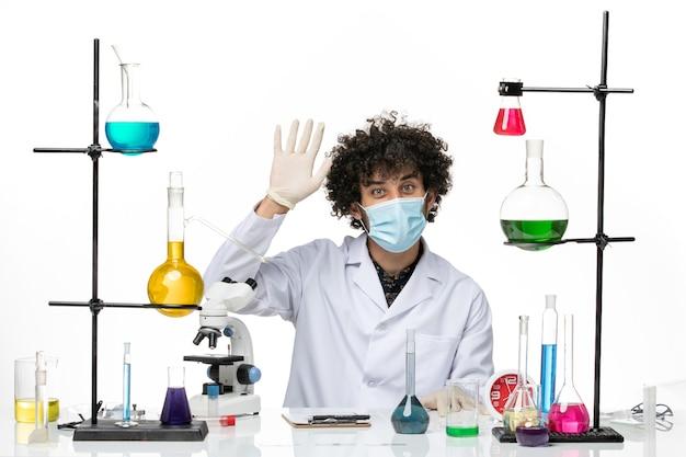 医療スーツを着て、白いスペースに手を振っているさまざまなソリューションとちょうど座っているマスクを持つ男性化学者の正面図