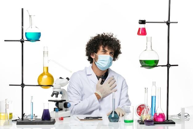 医療スーツを着て、明るい白いスペースにソリューションと一緒に座っているだけのマスクを持った正面図の男性化学者