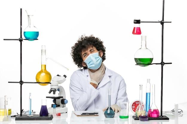 医療スーツを着て、白いスペースにソリューションと一緒に座っているだけのマスクを持った正面図の男性化学者