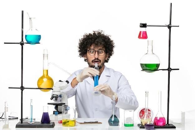 공백에 파란색 솔루션을 들고 의료 소송에서 전면보기 남성 화학자