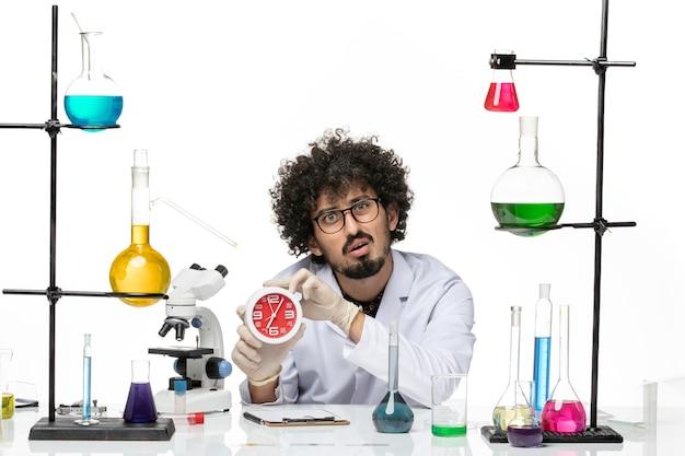 Вид спереди мужской химик в медицинском костюме, держа часы на белом пространстве