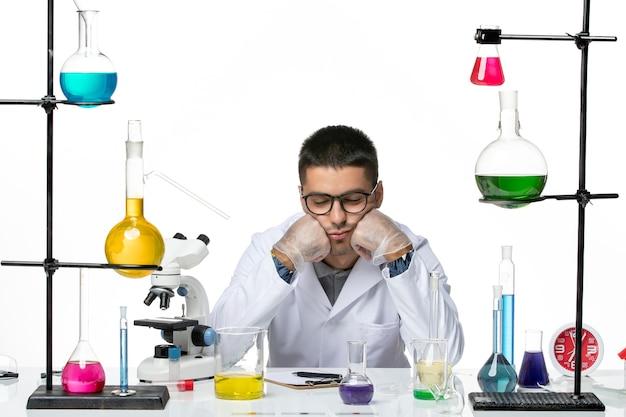 의료 소송에서 전면보기 남성 화학자 앉아서 흰색 배경 바이러스 covid 스플래시 질병 과학에 피곤 느낌