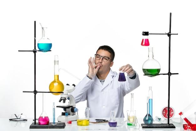 Вид спереди мужской химик в медицинском костюме сидит и держит фляжку с раствором на белом столе вирус covid splash болезнь наука