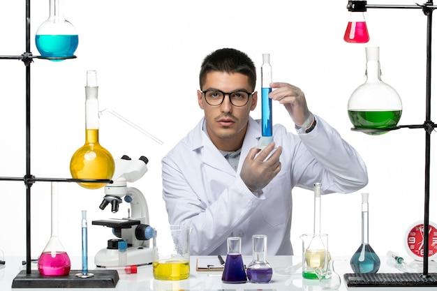 薄白の背景ウイルスcovid-スプラッシュ病気科学のソリューションを座って保持している医療スーツの正面図男性化学者