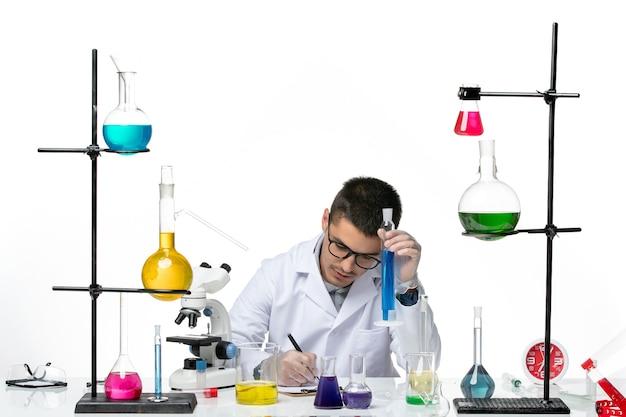 Вид спереди мужской химик в медицинском костюме сидит и держит раствор на белом столе вирус covid- splash болезнь наука