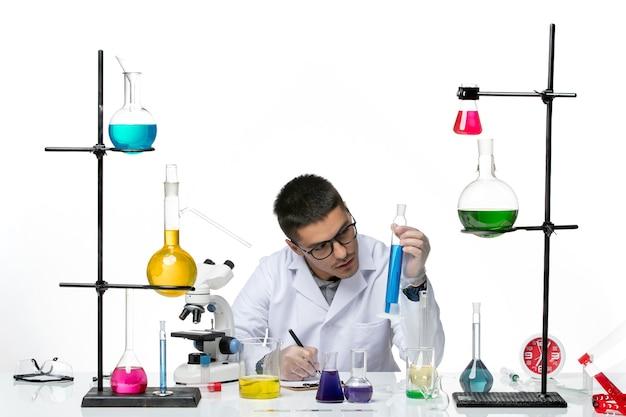 医療スーツを着た男性化学者が、白い背景のウイルスコビッドスプラッシュ病の科学に関するメモを書いているソリューションを座って保持している正面図