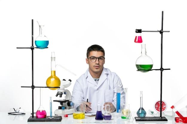 座って白い背景のウイルスcovidスプラッシュ病科学にメモを書いている医療スーツの正面図男性化学者