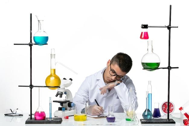 医療スーツを着た男性化学者が座って、明るい白の背景に何かを書いている正面図ウイルスcovidスプラッシュ病科学