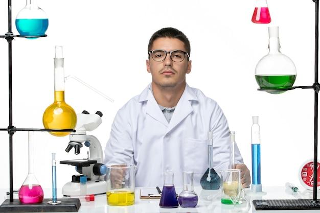 白い背景の上のさまざまなソリューションと座っている医療スーツの正面図男性化学者ウイルスラボ化学covid-スプラッシュ